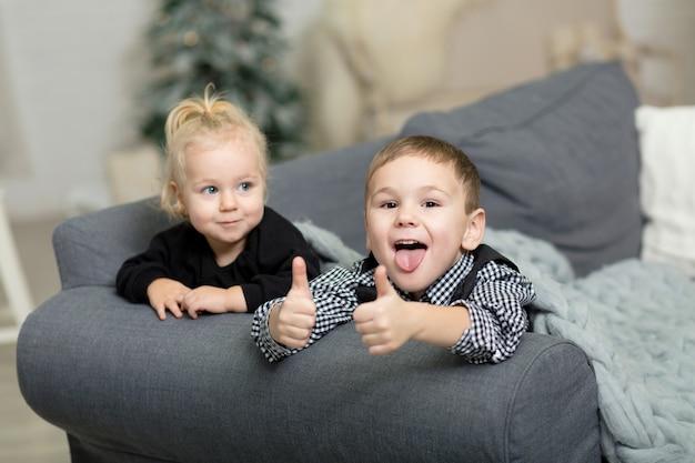 Menina e menino deitado t no sofá coberto com um cobertor de malha cinza e sorrindo.