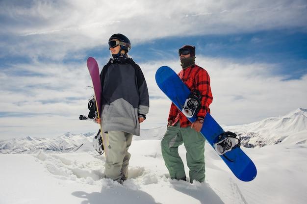 Menina e menino em pé nas montanhas com pranchas de snowboard
