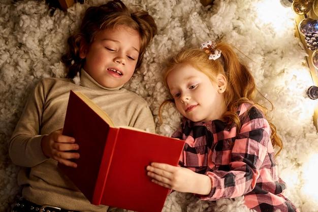Menina e menino estão lendo um livro em uma sala decorada para o natal.