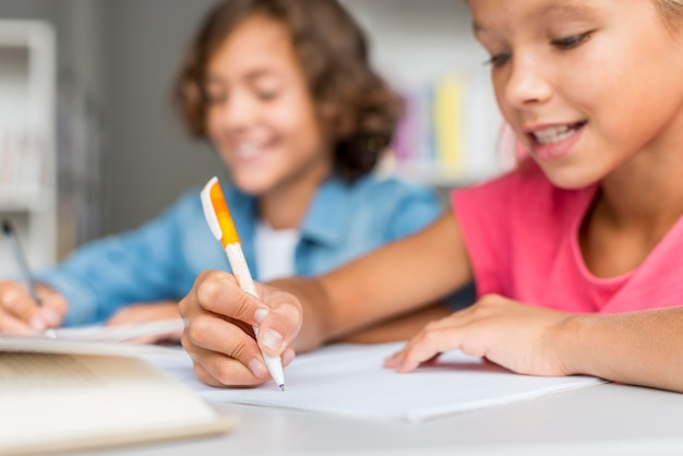 Menina e menino fazendo lição de casa juntos na biblioteca