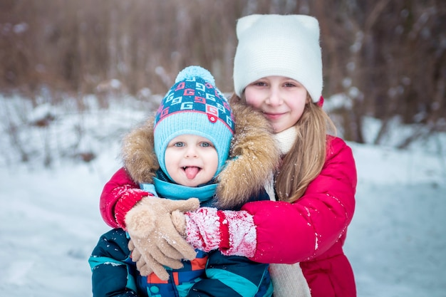 Menina e menino na floresta de inverno