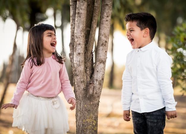 Menina e menino no parque. cara a cara gritando