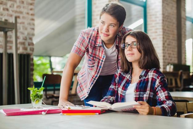 Menina e menino olhando longe com livros