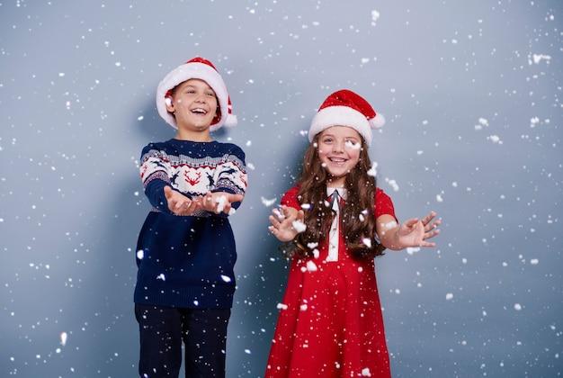 Menina e menino pegando snwoflakes