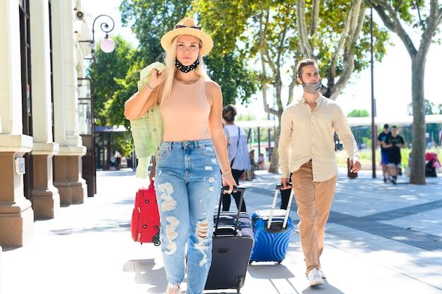 Menina e menino pretti andando em frente à estação de trem com a máscara facial - casal caminha com bagagem - novo conceito normal de viagem e estilo de vida