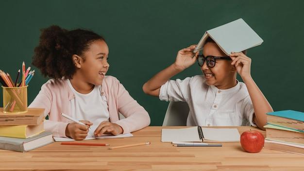 Menina e menino se divertindo com o material escolar