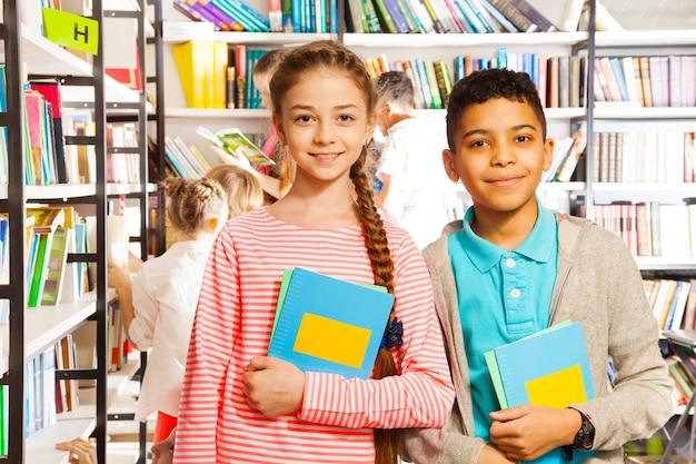Menina e menino sorrindo com livros