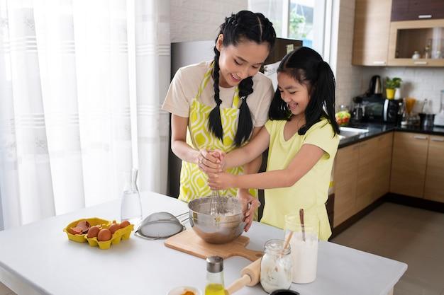 Menina e mulher de tiro médio preparando comida