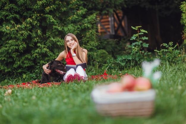 Menina e o cachorro dela sentado no jardim.