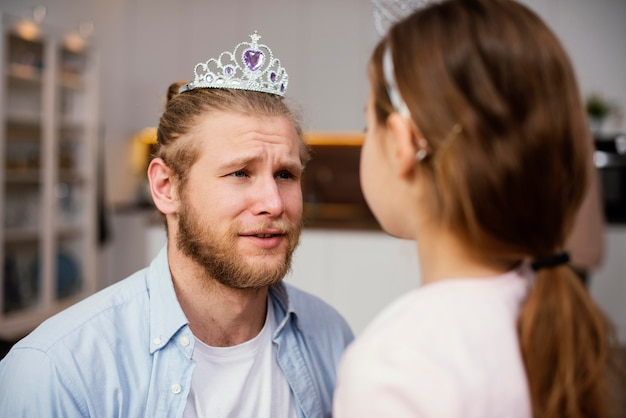Menina e pai brincando com tiara
