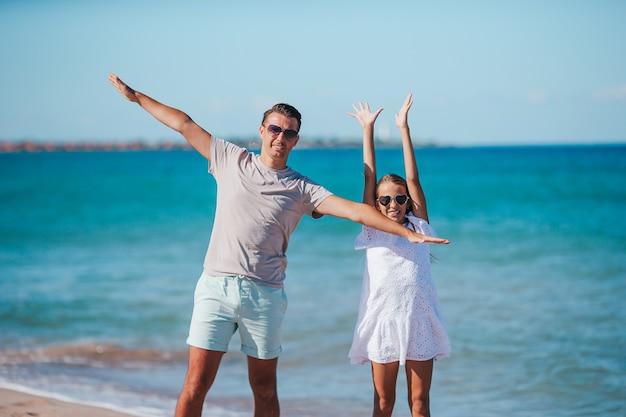 Menina e pai feliz se divertindo durante as férias na praia