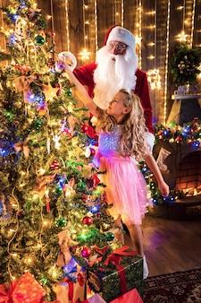 Menina e papai noel decoram a árvore de natal