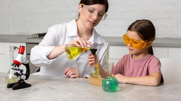 Menina e professora fazendo experiências científicas com microscópio e tubos de ensaio