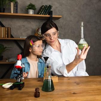 Menina e professora fazendo experiências científicas com tubos de ensaio e microscópio
