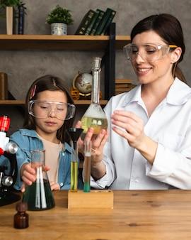 Menina e professora fazendo experiências científicas com tubos de ensaio