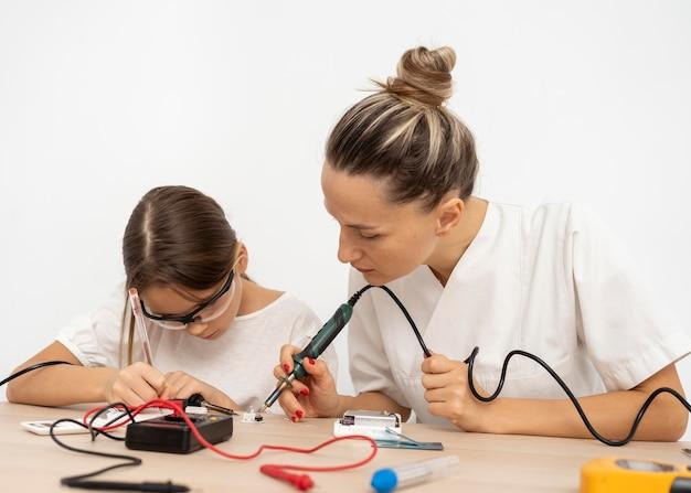 Menina e professora fazendo experiências científicas