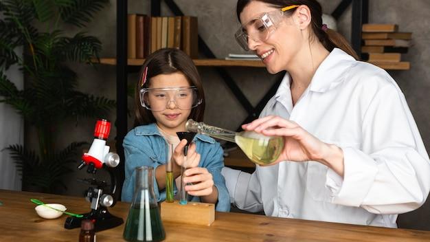 Menina e professora fazendo experimentos científicos
