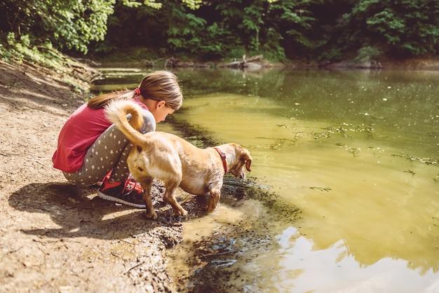 Menina e seu cachorro à beira do lago