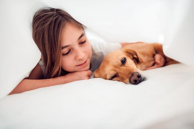 Menina e seu cachorro deitado na cama com cobertor