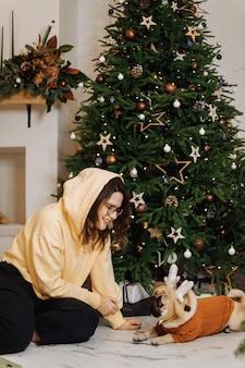 Menina e seu cachorro estão sentados perto da árvore de natal
