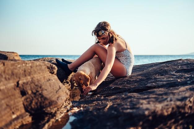 Menina e seu cachorro explorando a praia rochosa