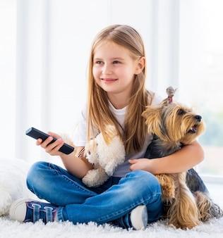 Menina e seu cachorro trocando de canal