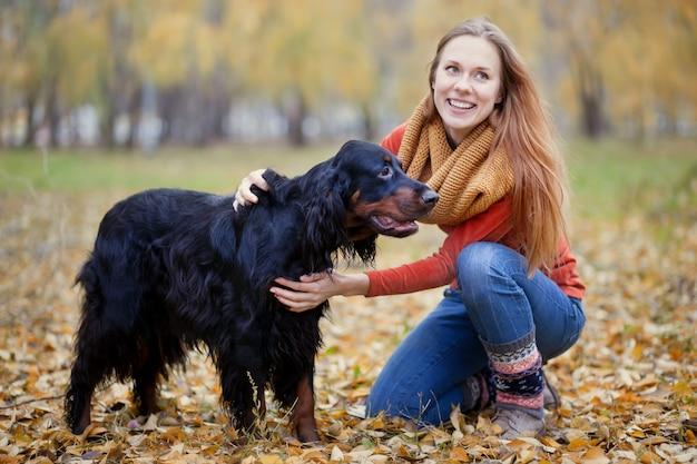 Menina e seu cão gordon setter no parque outono