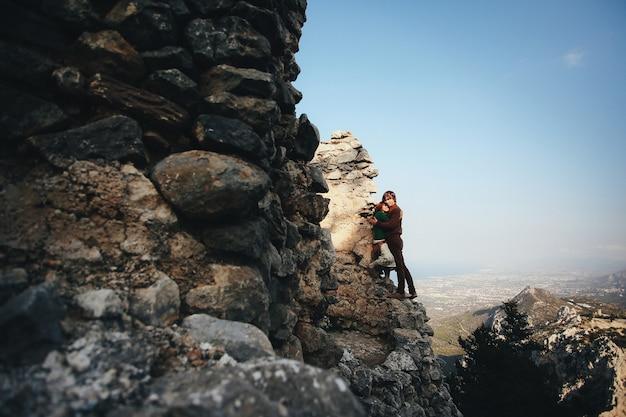 Menina e seu namorado estão abraçando, inclinando-se para a rocha na paisagem