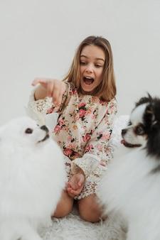 Menina e seus cachorros recebendo guloseimas