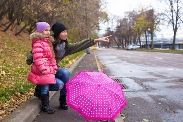 Menina e sua mãe andando com guarda-chuva em um dia chuvoso