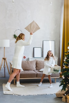 Menina e sua mãe brincando com travesseiro, interior é decorado para o natal