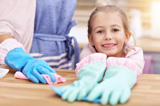 Menina e sua mãe em aventais se divertindo limpando a cozinha