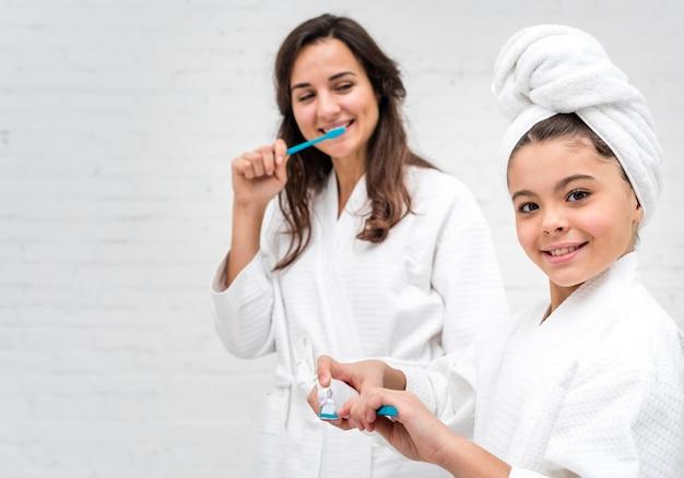 Menina e sua mãe escovando os dentes