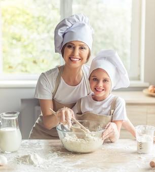 Menina e sua mãe linda em aventais e chapéus de cozinha.