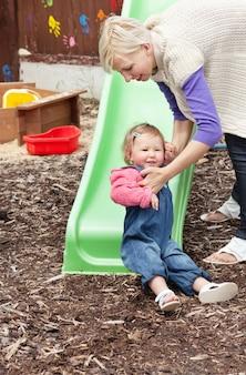 Menina e sua mãe loira se divertindo com uma calha