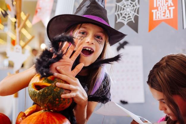 Menina e truques. garota de olhos escuros usando fantasia de feiticeiro de halloween, pregando peças enquanto participava da festa de comemoração