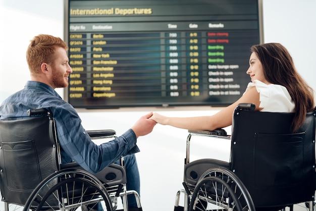 Menina e um cara em cadeiras de rodas perto do horário dos voos.