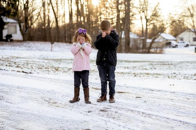 Menina e um menino em pé e orando durante o pôr do sol