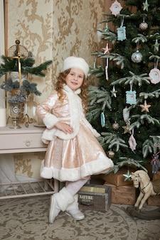 Menina e uma manhã de natal, uma criança posando na árvore de natal