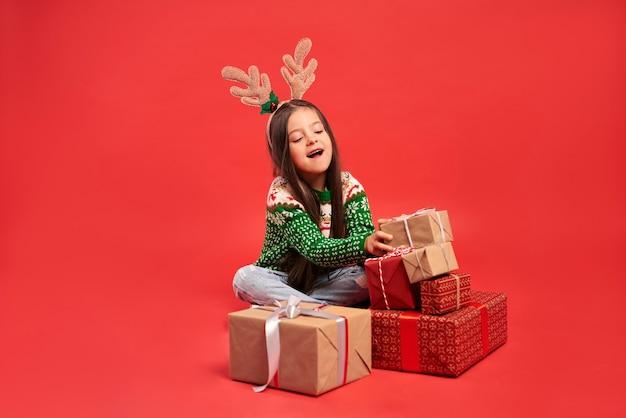 Menina e uma pilha de presentes de natal