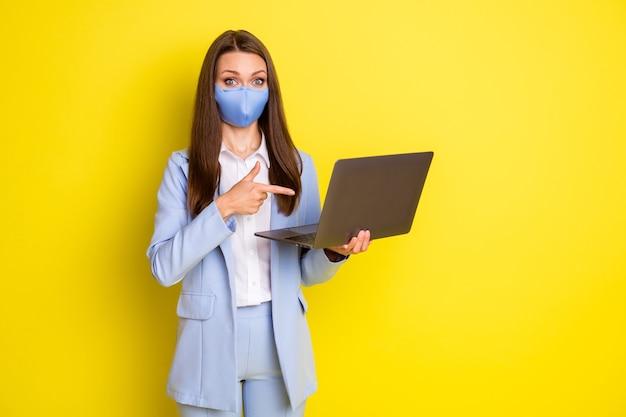 Menina economista chocada em máscara respiratória trabalho dedo ponto remoto laptop presente notícias quarentena cobiçado usar blazer blazer azul calça calça isolada brilhante cor de fundo