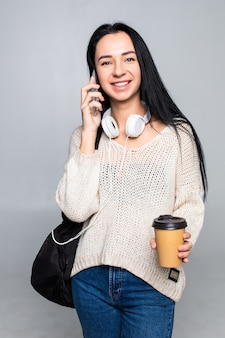 Menina elegante atraente rindo alegremente enquanto fala no telefone celular com o namorado, isolado na parede cinza. conceito de conversa.