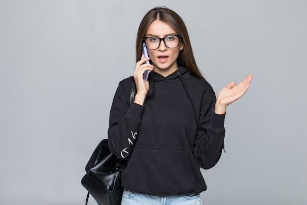 Menina elegante atraente rindo alegremente enquanto fala no telefone celular com o namorado, isolado na parede cinza.
