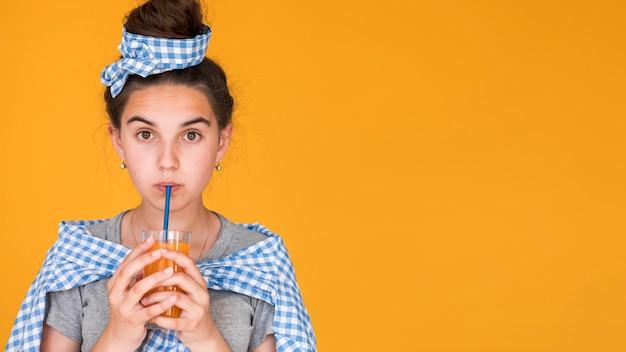 Menina elegante, bebendo suco de laranja com espaço de cópia