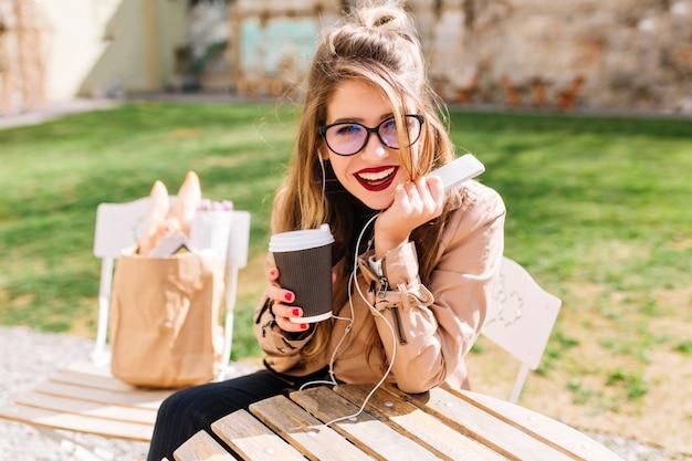 Menina elegante branca em copos grandes bebe café no parque e ouve música em fones de ouvido com interesse, olhando para a câmera. pausa para o café no café ao ar livre, depois das compras.