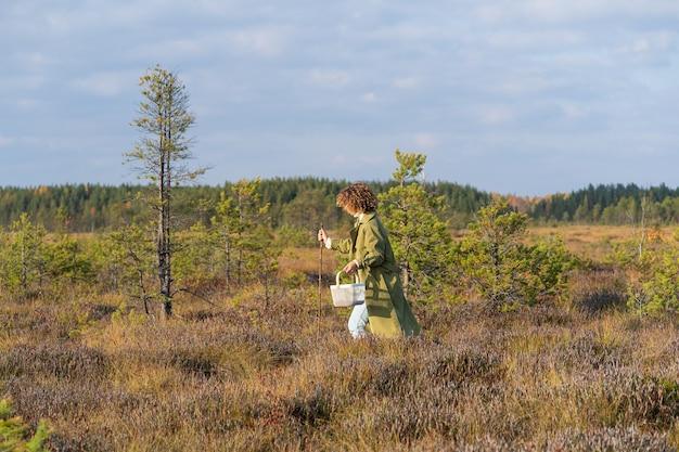 Menina elegante caminhando no pântano colhendo cranberries e outras frutas sazonais no fim de semana ou nas férias