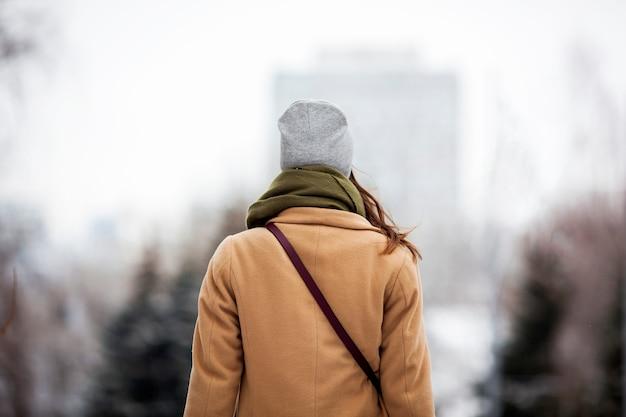 Menina elegante casaco bege com cachecol e uma bolsa de chapéu