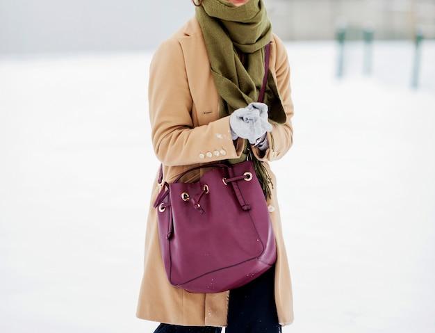 Menina elegante casaco bege com cachecol e uma bolsa