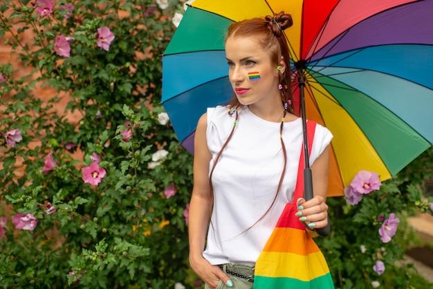 Menina elegante com bandeira lgbt no rosto, posando com guarda-chuva de arco-íris