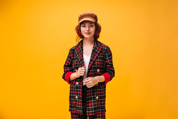 Menina elegante com casaco xadrez posando na parede laranja